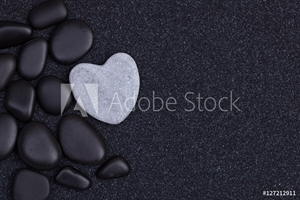 Picture of Black stones with grey zen heart shaped rock on  grain sand
