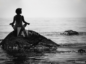 Picture of  young woman sits in a lotus position on a large stone in the sea and meditates, her fingers are folded in Prithivi mudra.