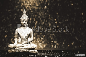 Picture of Buddha statue on a bright shiny background with bokeh. Photo in vintage style