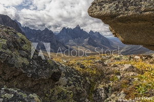 Picture of Tombstone Mountain is framed by rocks in this view within Tombstone Territorial Park; Yukon, Canada