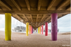Picture of Shot under pier with color painted columns on the beach at sunset.