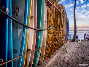 Picture of Colourful surfboards stacked up on Waikiki Beach at sunset.