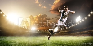 Picture of Soccer player in action on sunset stadium panorama background