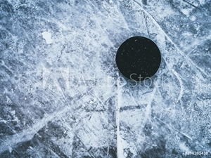 Picture of hockey puck on the ice and snow texture, copyspace and text